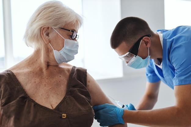 Mulher idosa e médico hospitalar imunidade cobiçada com vacina