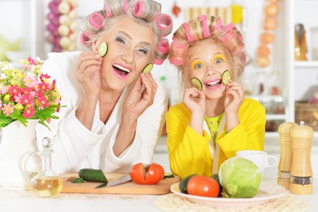 Mulher idosa e neta na cozinha com legumes