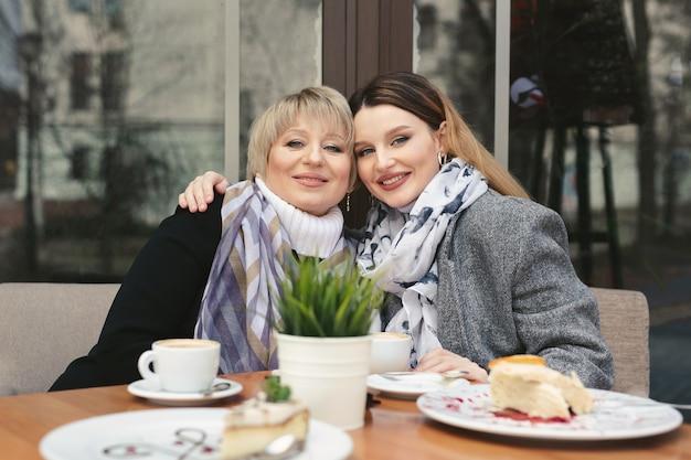 Mulher idosa e sua filha adulta tomando café