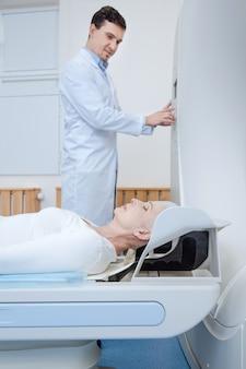 Mulher idosa e tranquila deitada em uma mesa de exame e fechando os olhos enquanto é examinada no laboratório