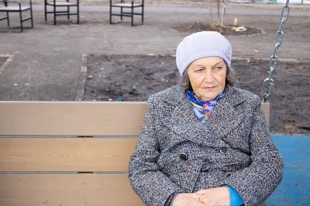 Mulher idosa e triste descansando em um balanço ao ar livre em close da primavera