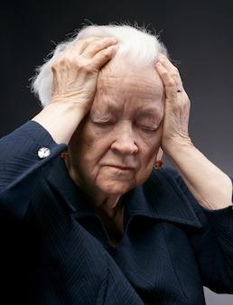 Mulher idosa e triste posando em estúdio sobre fundo cinza