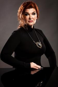 Mulher idosa elegante com cabelo vermelho em um vestido preto com um medalhão mágico em volta do pescoço.
