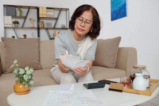 Mulher idosa elegante e pensativa de óculos verificando contas e calculando despesas ao beber chá na sala de estar