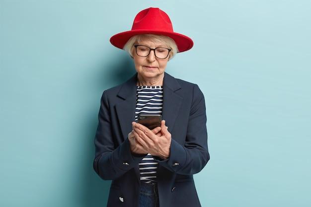 Mulher idosa elegante envia mensagens de texto no smartphone, satisfeita com as tarifas na internet, faz compras online, escolhe roupas novas na loja da web, usa um capacete vermelho elegante, óculos e jaqueta formal