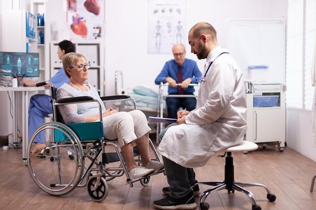 Mulher idosa em cadeira de rodas em consulta médica na clínica de recuperação