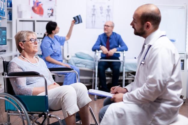 Mulher idosa em cadeira de rodas falando sobre reabilitação para deficientes físicos com médico na clínica de recuperação