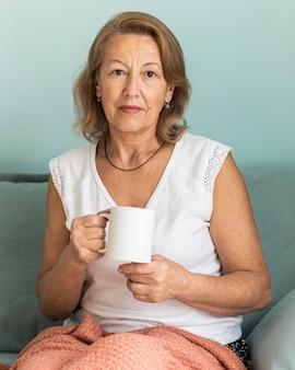 Mulher idosa em casa durante a pandemia tomando uma xícara de café