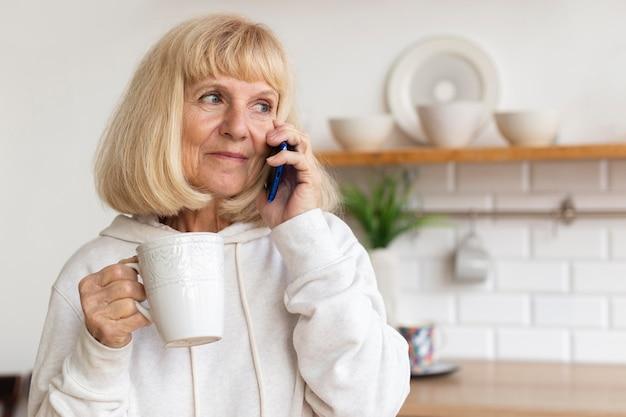 Mulher idosa em casa falando ao telefone enquanto toma café