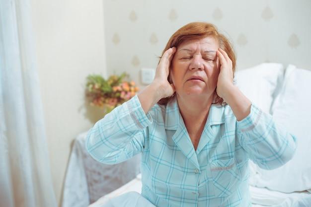 Mulher idosa em casa na cama com dor de cabeça. a avó ruiva tem um problema de saúde