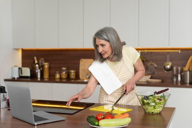 Mulher idosa em casa na cozinha, tendo aulas de culinária no laptop
