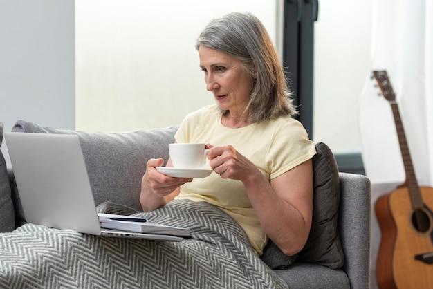 Mulher idosa em casa no sofá usando laptop e tomando café