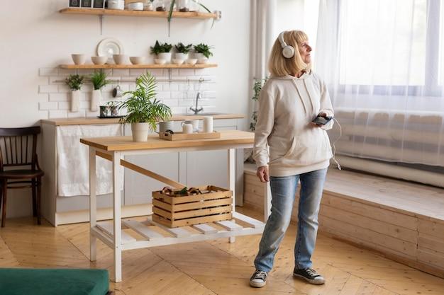 Mulher idosa em casa ouvindo música em fones de ouvido e usando smartphone
