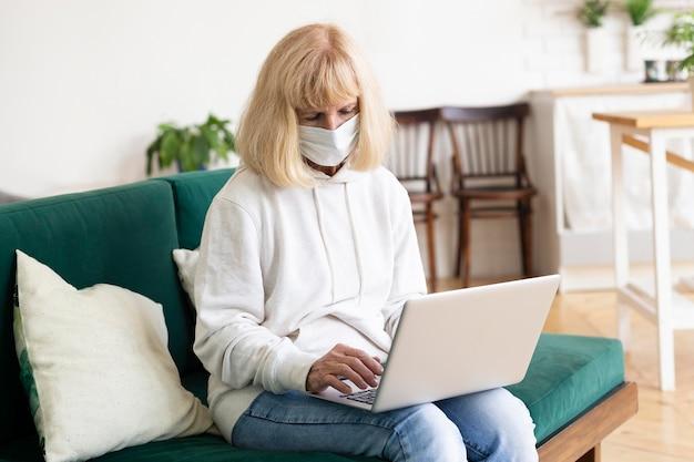 Mulher idosa em casa trabalhando em um laptop com máscara médica