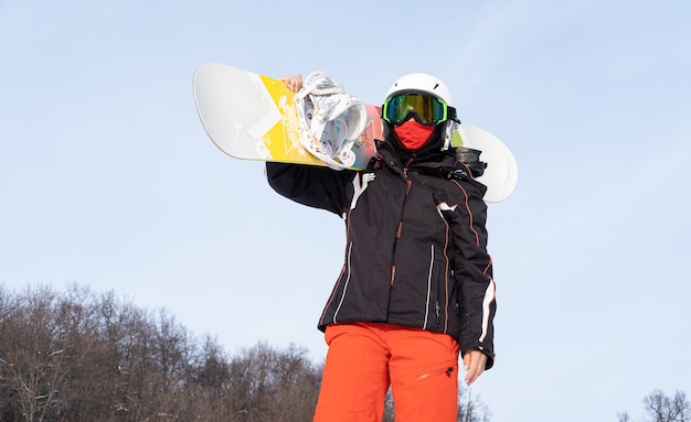 Mulher idosa em esportes usa capacete, óculos, máscara protetora, segurando snowboard no ombro