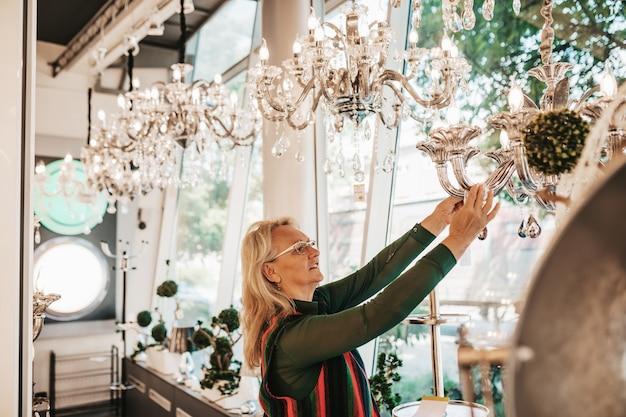 Mulher idosa em loja de iluminação doméstica fotografando o shandelier para sua casa