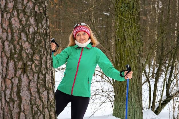 Mulher idosa em pé com bastões de caminhada nórdica na floresta de inverno