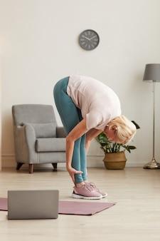 Mulher idosa em pé e alongando o corpo durante o treinamento esportivo na sala de casa