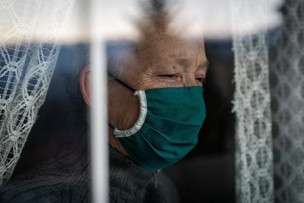 Mulher idosa em quarentena chorando na janela