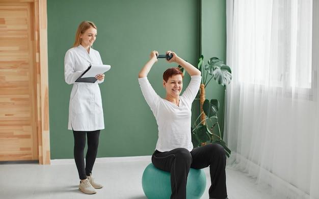 Mulher idosa em recuperação cobiçosa fazendo exercícios físicos com halteres enquanto a enfermeira verifica