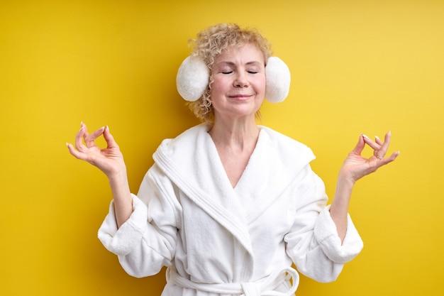 Mulher idosa em roupão de banho e fone de ouvido, mantenha a calma, namaste, isolada