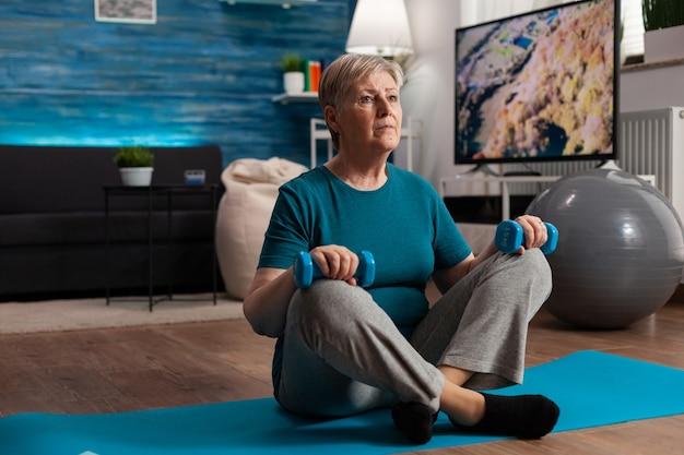 Mulher idosa em roupas esportivas aquecendo os músculos abdominais, praticando exercícios corporais de academia