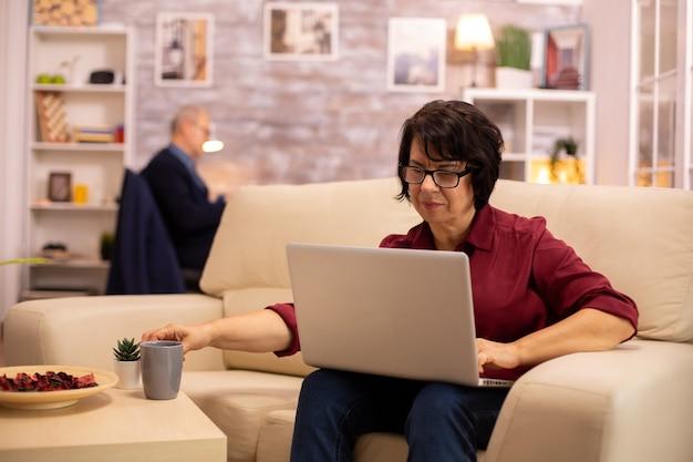 Mulher idosa em seu sofá, trabalhando em um laptop moderno em sua aconchegante sala de estar. o marido dela está no fundo
