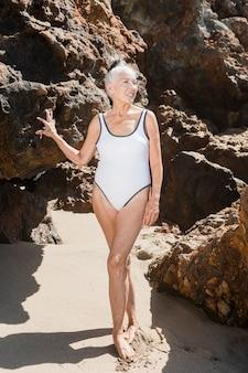 Mulher idosa em traje de banho branco de uma peça só, ensaio fotográfico