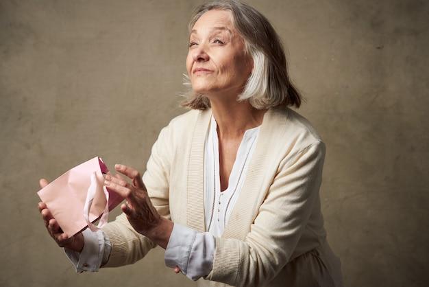 Mulher idosa em um roupão com um presente nas mãos.