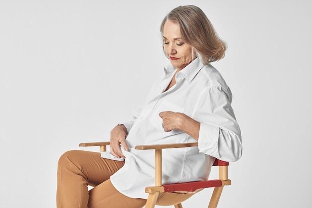Mulher idosa em uma camisa branca sentada em uma cadeira com os lábios vermelhos isolados no fundo