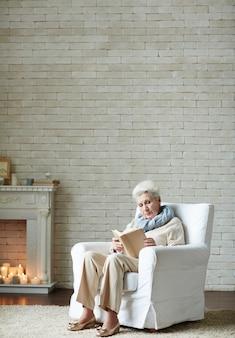 Mulher idosa embrulhada na leitura