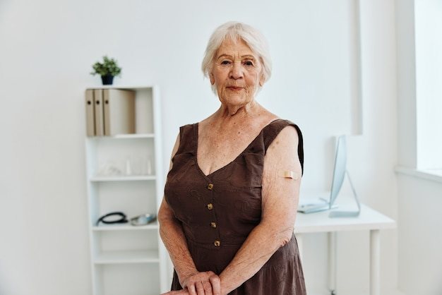 Mulher idosa emocional com um emplastro no passaporte da vacina da mão covid