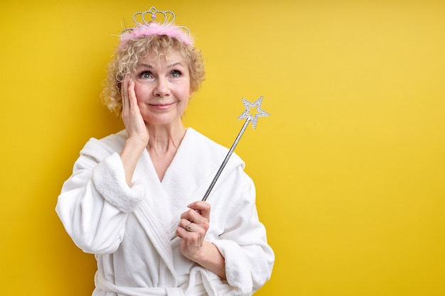 Mulher idosa encantadora em roupão de banho com coroa na cabeça, segurando a varinha mágica nas mãos, fada sênior, tocando as bochechas do rosto de surpresa