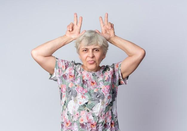 Mulher idosa engraçada coloca as mãos na cabeça gesticulando chifres e mostra a língua isolada na parede branca