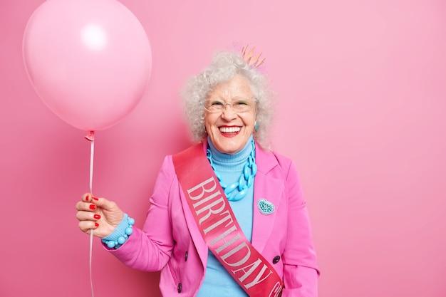 Mulher idosa enrugada, com cabelo encaracolado e balão inflado, comemora aniversário
