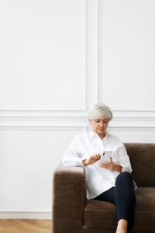 Mulher idosa enviando mensagens de texto no telefone em casa