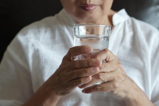 Mulher idosa está comendo remédio e com pílulas e copo de água em casa