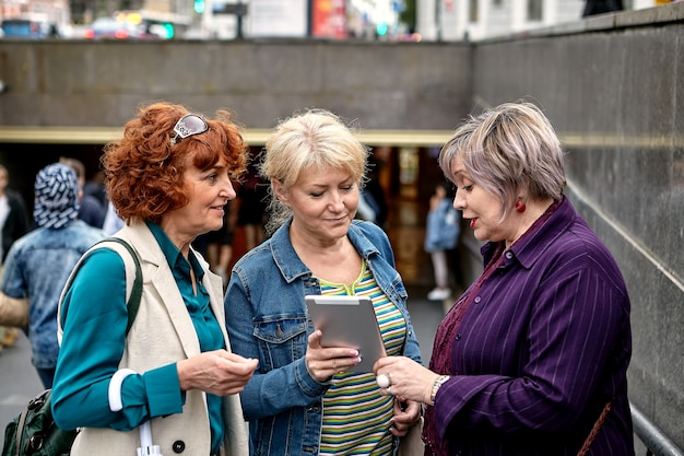 Mulher idosa está mostrando fotos na tela do tablet pc para suas amigas perto da passagem subterrânea.