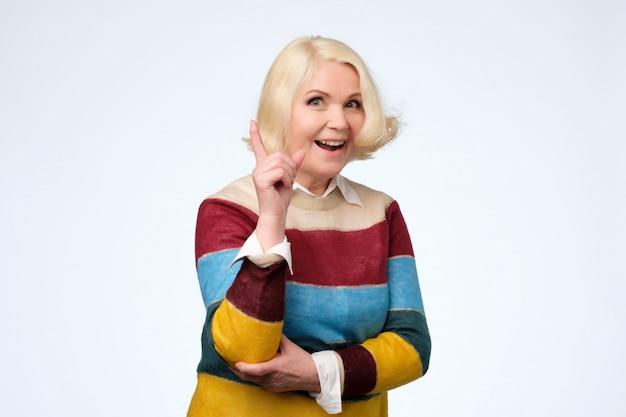 Mulher idosa expressiva e emocional apontando com o dedo indicador para cima
