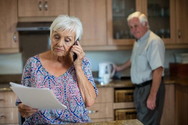 Mulher idosa falando ao telefone enquanto homem trabalha na cozinha de casa