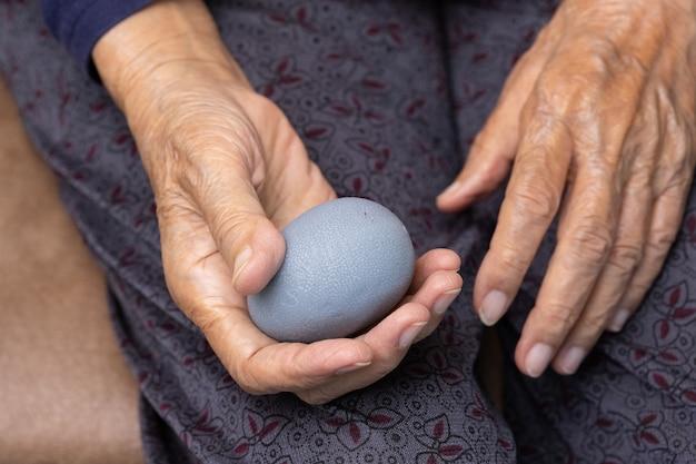 Mulher idosa fazendo bola de borracha para exercícios de dedos, palma, mão e músculo do pé com cuidador cuidar.