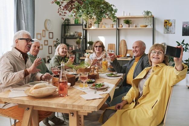 Mulher idosa fazendo selfie com seus velhos amigos no celular enquanto eles estão sentados à mesa durante o jantar