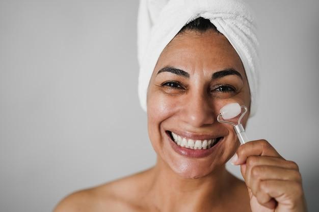 Mulher idosa fazendo tratamento de cuidados com a pele usando rolo facial - foco principal nos olhos