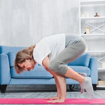 Mulher idosa fazendo yoga na sala de estar