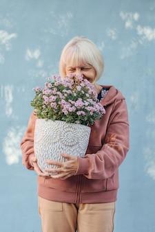 Mulher idosa feliz cheirando flores. mulher sênior alegre sorrindo e cheirando flores em vasos