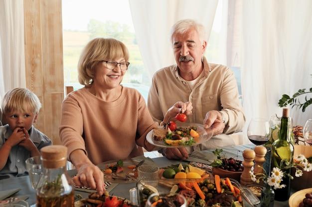 Mulher idosa feliz colocando legumes no prato do marido enquanto eles estão sentados à mesa durante o jantar de feriado