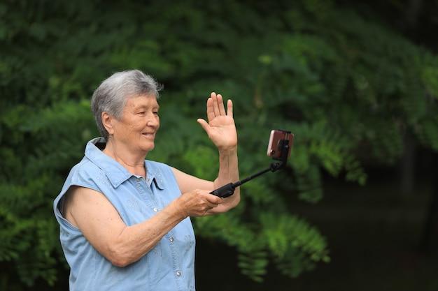 Mulher idosa feliz com deficiência ao ar livre no parque de verão e falando ao telefone