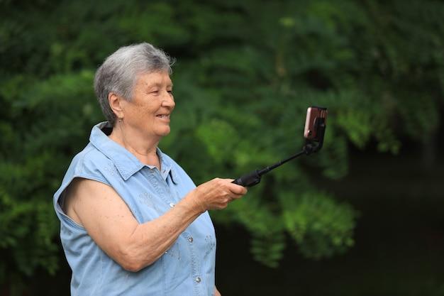 Mulher idosa feliz com deficiência ao ar livre no parque falando ao telefone