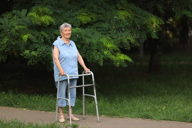 Mulher idosa feliz com deficiência caminhando com andador ao ar livre no verão