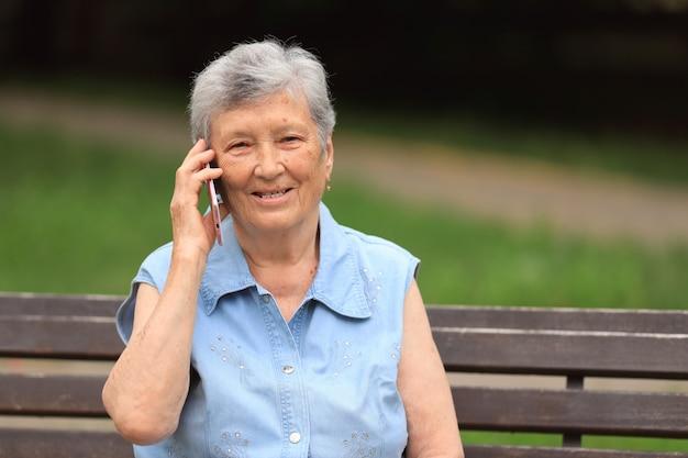 Mulher idosa feliz com deficiência, sentada em um banco ao ar livre em um parque de verão e falando ao telefone